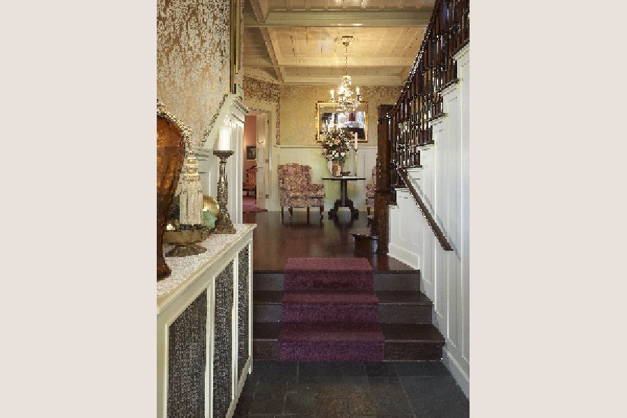 Victorian hallway with a chandelier and a small security lamp