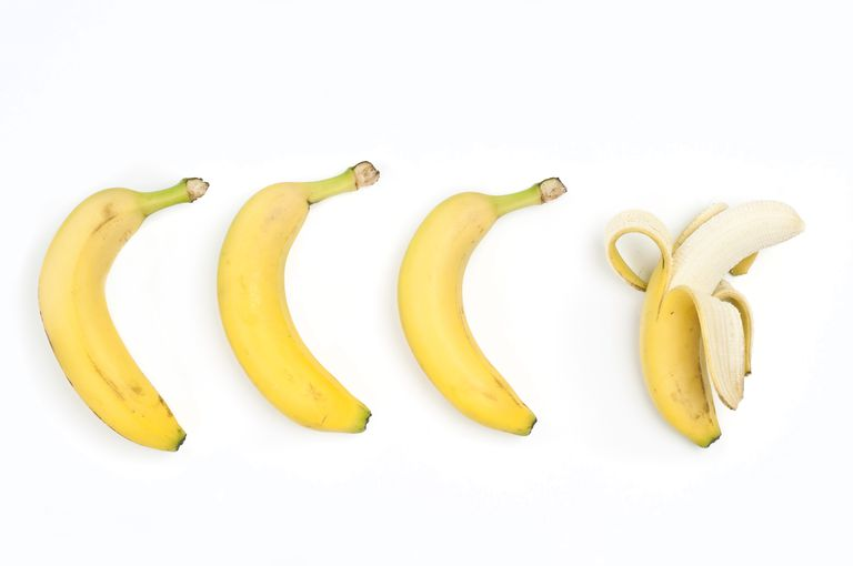 Three bananas with their skin on, and one peeled banana