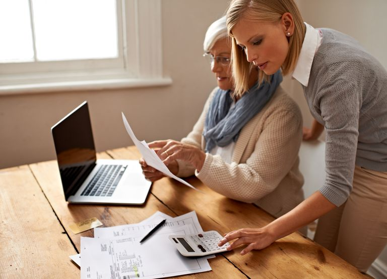 Cropped view of a senior woman receiving help with her finances from her granddaughter