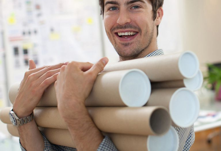 Smiling man holding tubes of architectural drawings