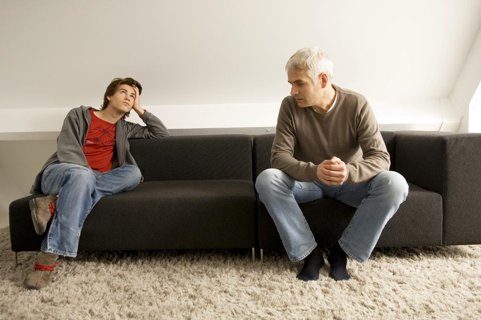 Mature man and his son sitting on a couch