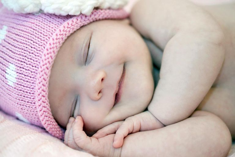Baby girl with smiley face in pink hat.