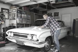 Young man waxing classic car in garage