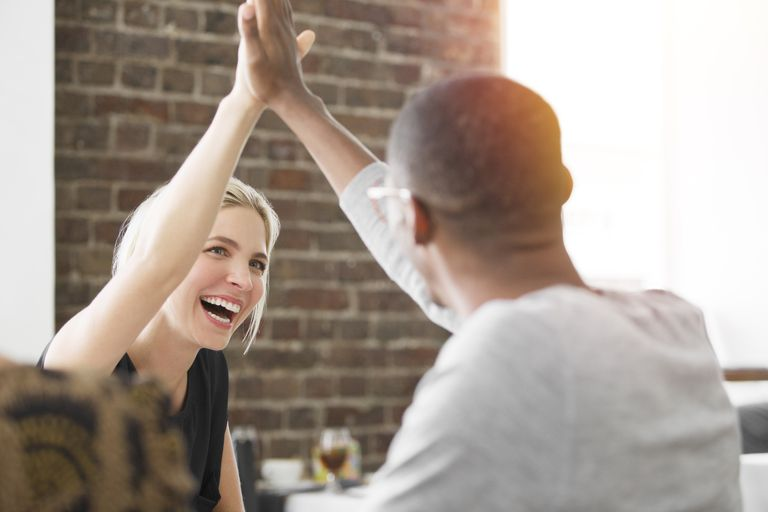 Business people high fiving at meeting in cafe