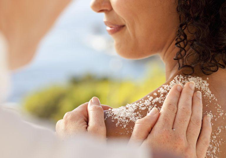 Young woman enjoying a salt scrub at a spa.