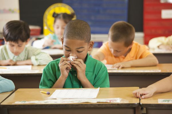 Boy blowing his nose in school