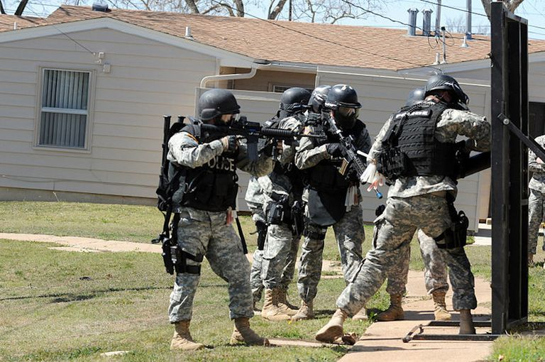 A Special Reaction Team of 178th Military Police Detachment, 89th MP Brigade, force their way into a condemned house on post during new a training exercise March 5.