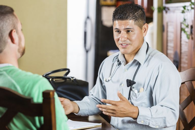 Friendly physician talking with patient during house call appointment