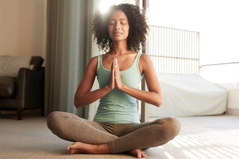 A woman meditates at home