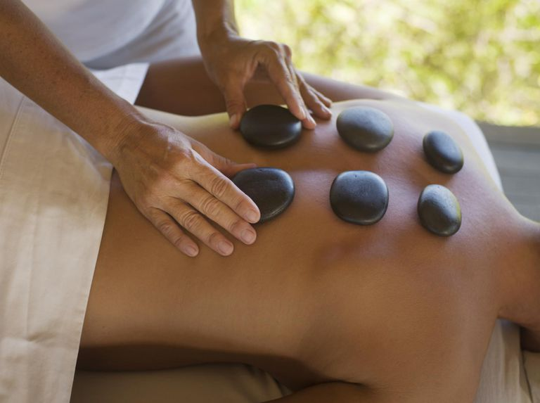Woman receiving hot stone therapy, mid section, close up