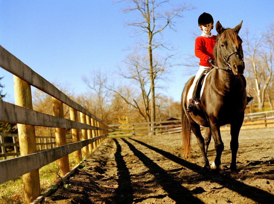 Girl (7-9) riding horse, wearing riding habit