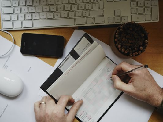 man writing check in front of computer