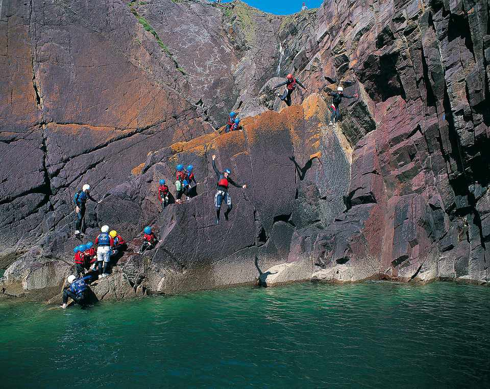 Coasteering off cliffs in Pembrokeshire, Wales, United Kingdom