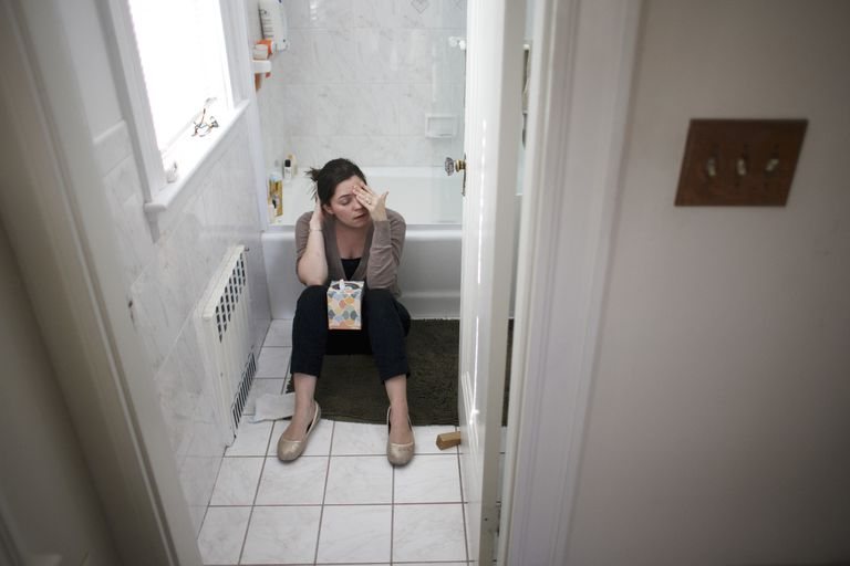 Pregnant Woman Sitting on Bathroom Floor with Box of Tissues between Knees
