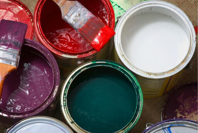 Open cans of colour paint, with paintbrush