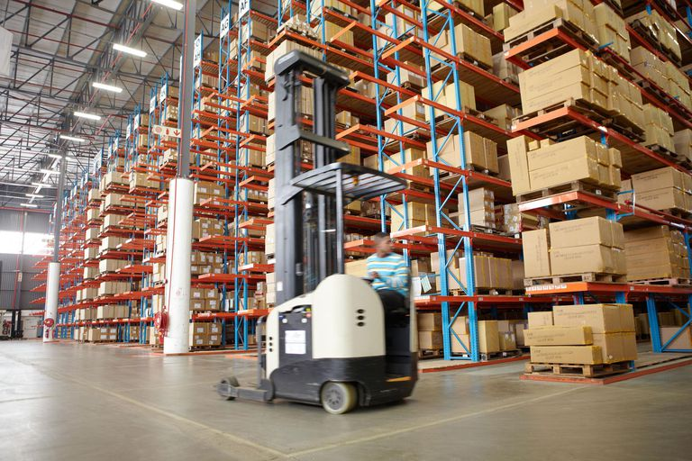 Worker driving forklift truck inside a warehouse