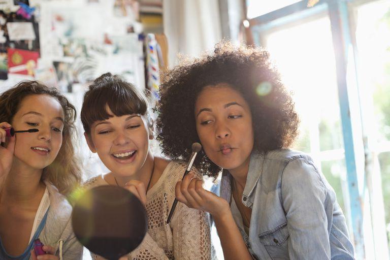 Women applying makeup in bedroom