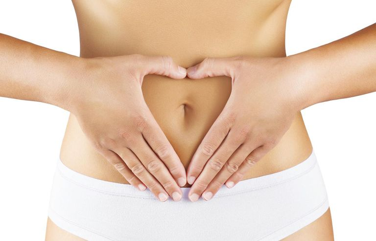 woman placing hands over stomach in shape of heart
