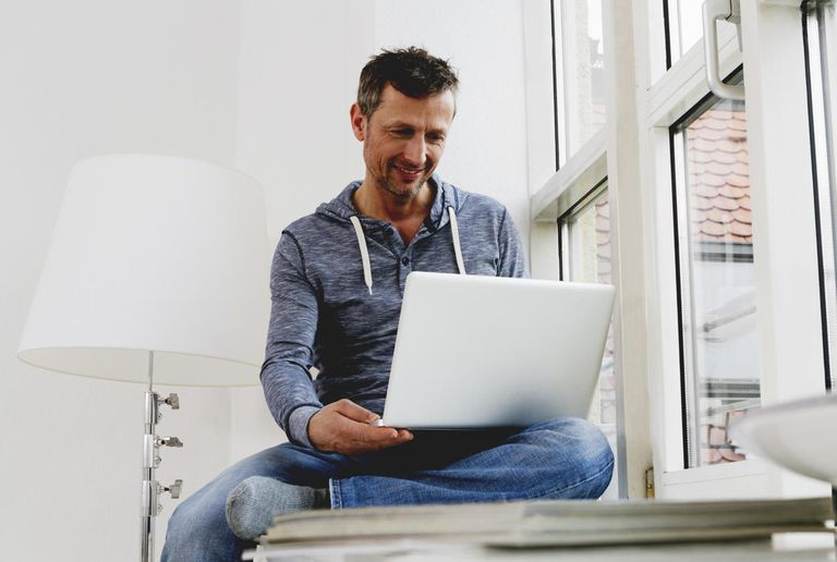 Man sitting on windowsill using laptop
