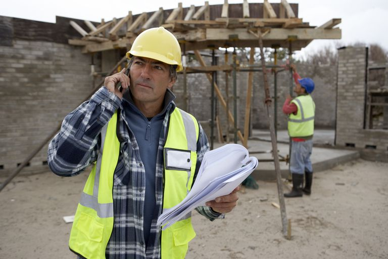 builder using phone on construction site alistair berg getty images job searching cover letters