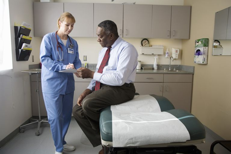 Female nurse talking to male patient