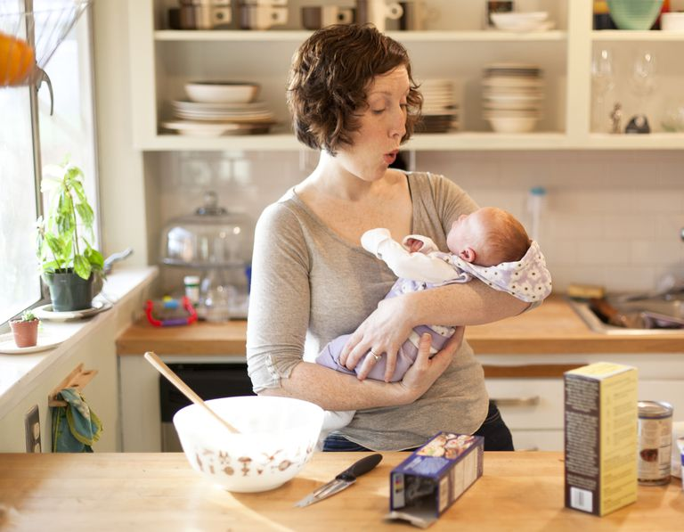 Woman making face at her baby while preparing food in the kitchen