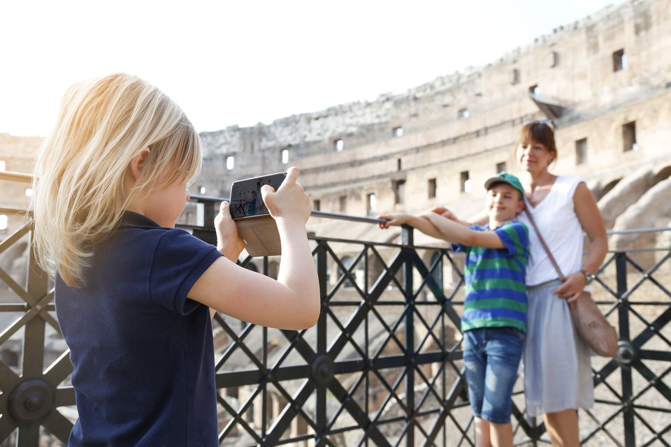 Italy, Rome, little girl taking picture of mother and brother with smartphone