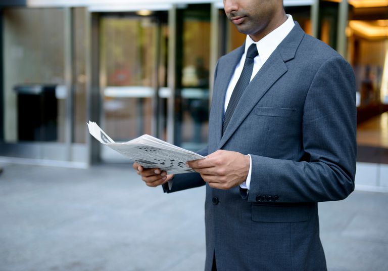 Businessman reading a newspaper outside building