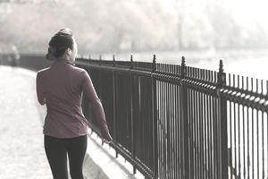 Woman walking along fence, water, trees