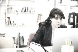 Young woman sitting at desk, using laptop