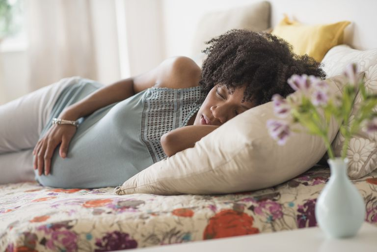Pregnant African American mother holding her stomach in bed