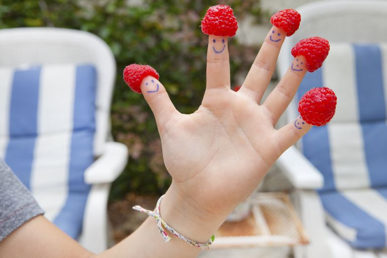 Woman with smiley faces and raspberry hats on the fingers of her left hand