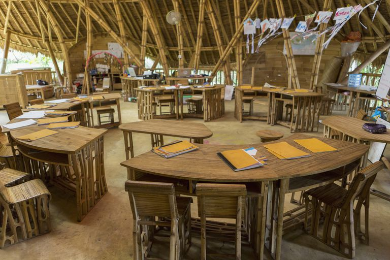 Circular desks in bamboo classroom, open air and light in a circular building without doors or windows