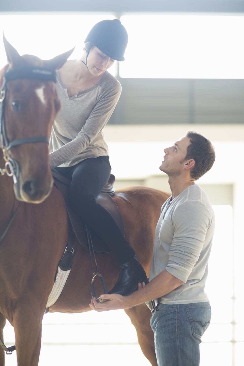 Female horseback rider with instructor in indoor paddock