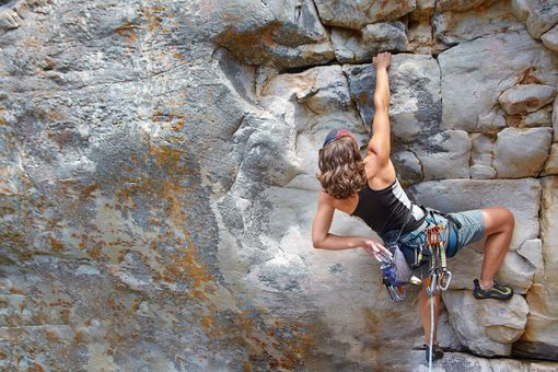 Rear view of a female rock climber scaling a rock face
