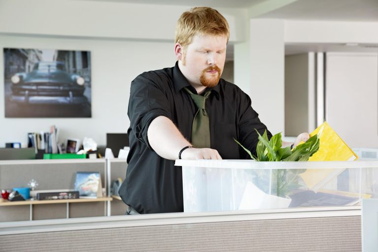 man in cubicle packing stuff into a container