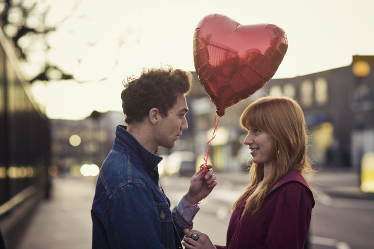 A couple in love in the city, the man handing the woman a heart-shaped baloon.