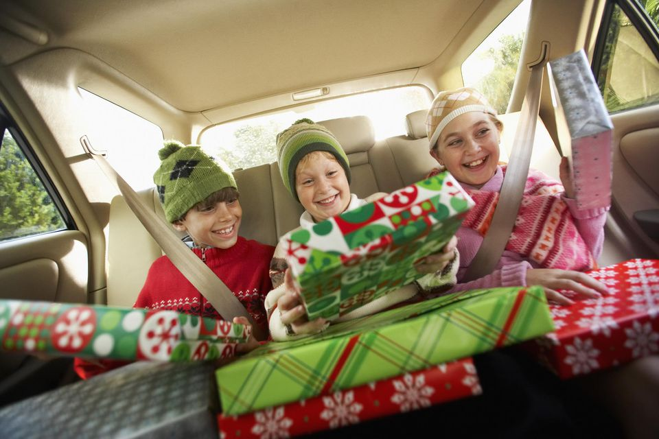 A picture of a family with presents in a car