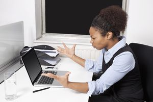 Side view of frustrated young businesswoman looking at laptop in office