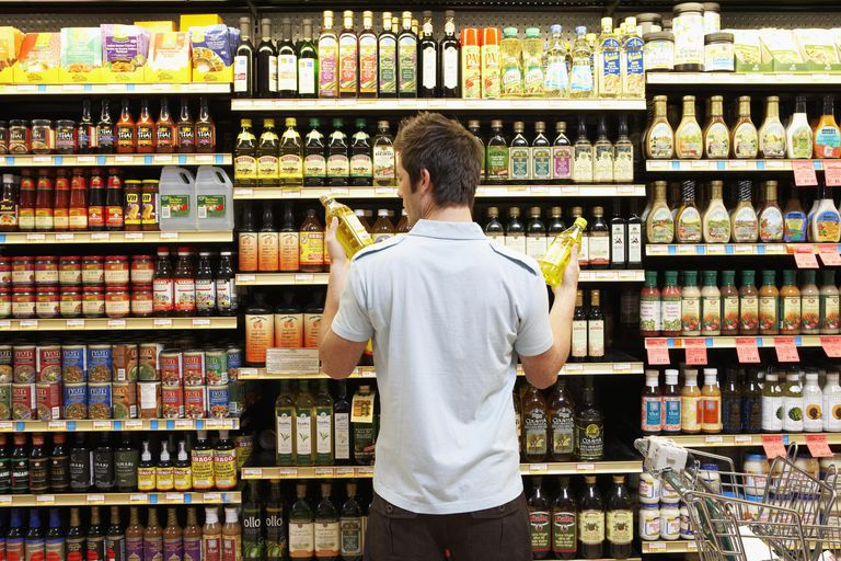 Young man in supermarket comparing bottles of oil