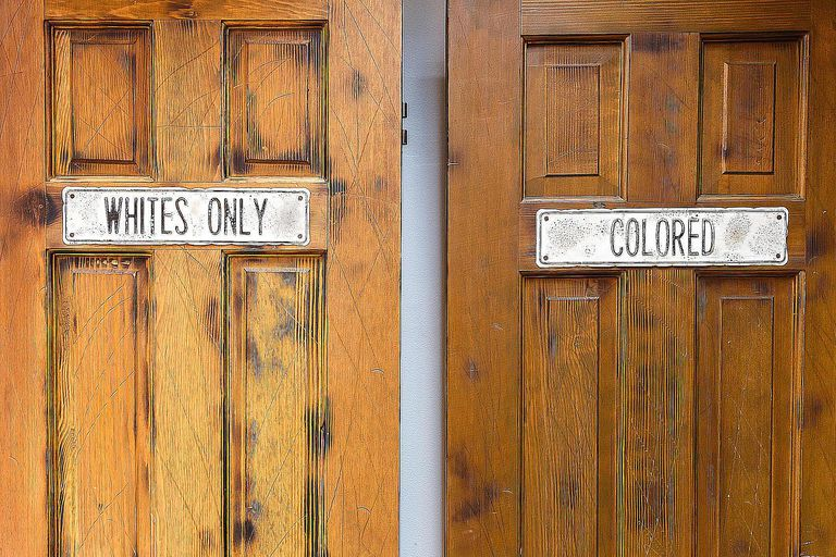"Doors marked ""whites only"" and ""colored"" signal both prejudice and racism. Learn the difference between the two here."
