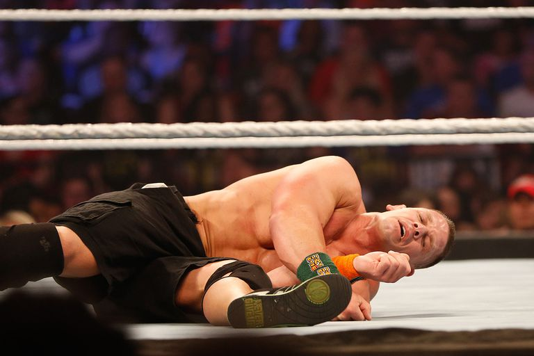 John Cena recovers from a blow during his fight against Seth Rollins at the WWE SummerSlam 2015 at Barclays Center of Brooklyn on August 23, 2015 in New York City.