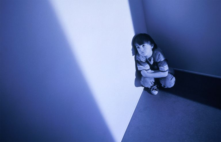 Boy crouched in corner of room.