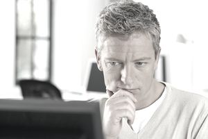 man thinking in front of computer