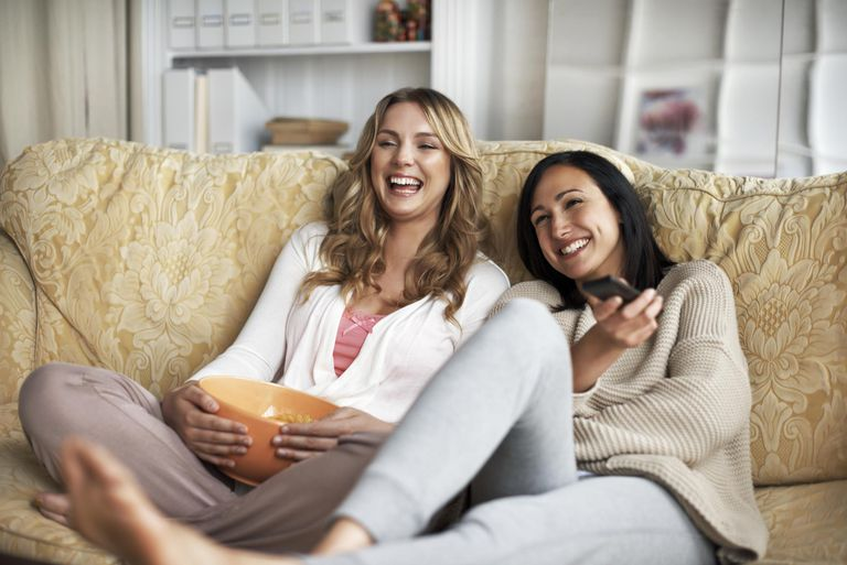 Woman sitting on sofa watching Tv