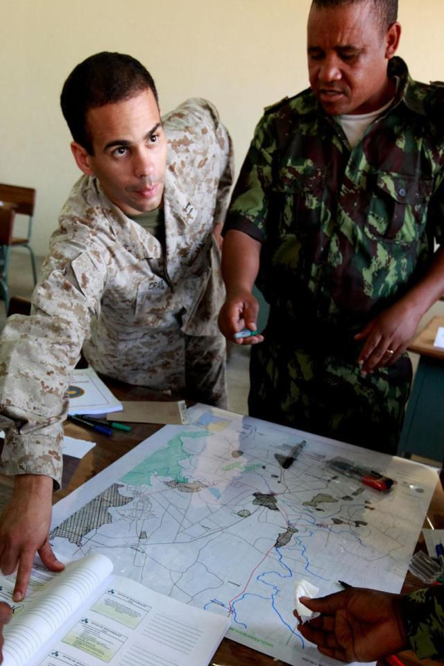 MOAMBA, Mozambique (July 30, 2010) – Capt. Wilfredo Crave, a Marine Forces Africa intelligence officer, helps Mozambican officers and senior enlisted identify key terrain features on a map as part of an intelligence-mentoring package July 30, 2010. The package will culminate with a command post exercise wherein Mozambican leaders must coordinate troops on the ground participating in the final field training exercise of SHARED ACCOURD 2010, a Marine Forces Africa bilateral exercise with the Forces for the Defense of Mozambique.