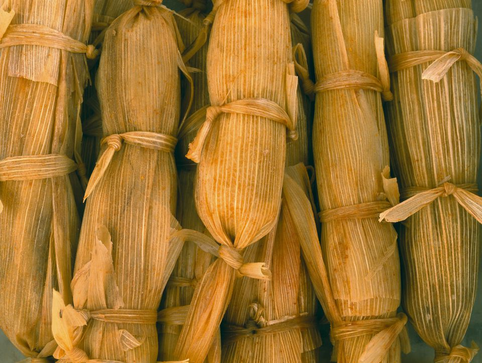 Mexican steamed tamales wrapped in dried corn husks, close-up