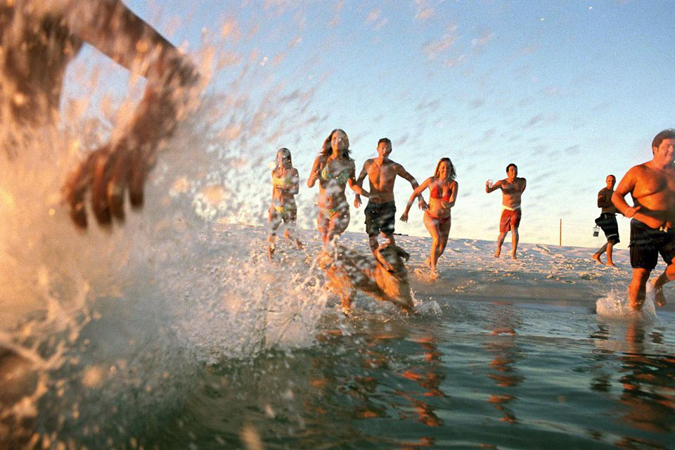 Group of young adults running through water at ocean's shore