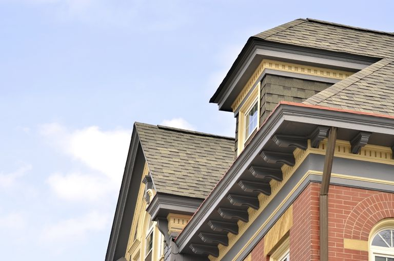 view of top of house, with window dormer and gable, looking up under the roof overhang with corbels