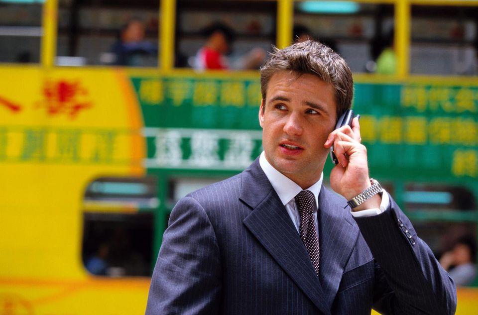 Businessman in Street on Mobile Phone, Hong Kong